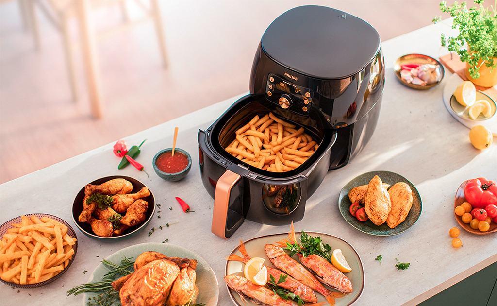 Voll gedeckter Tisch mit Essen und Philips Airfryer