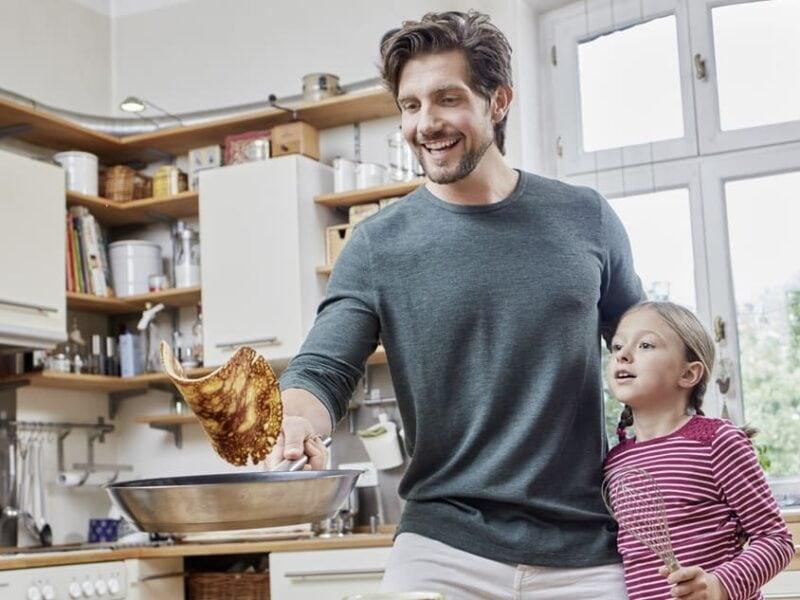 Vater und Tochter braten Eierkuchen.