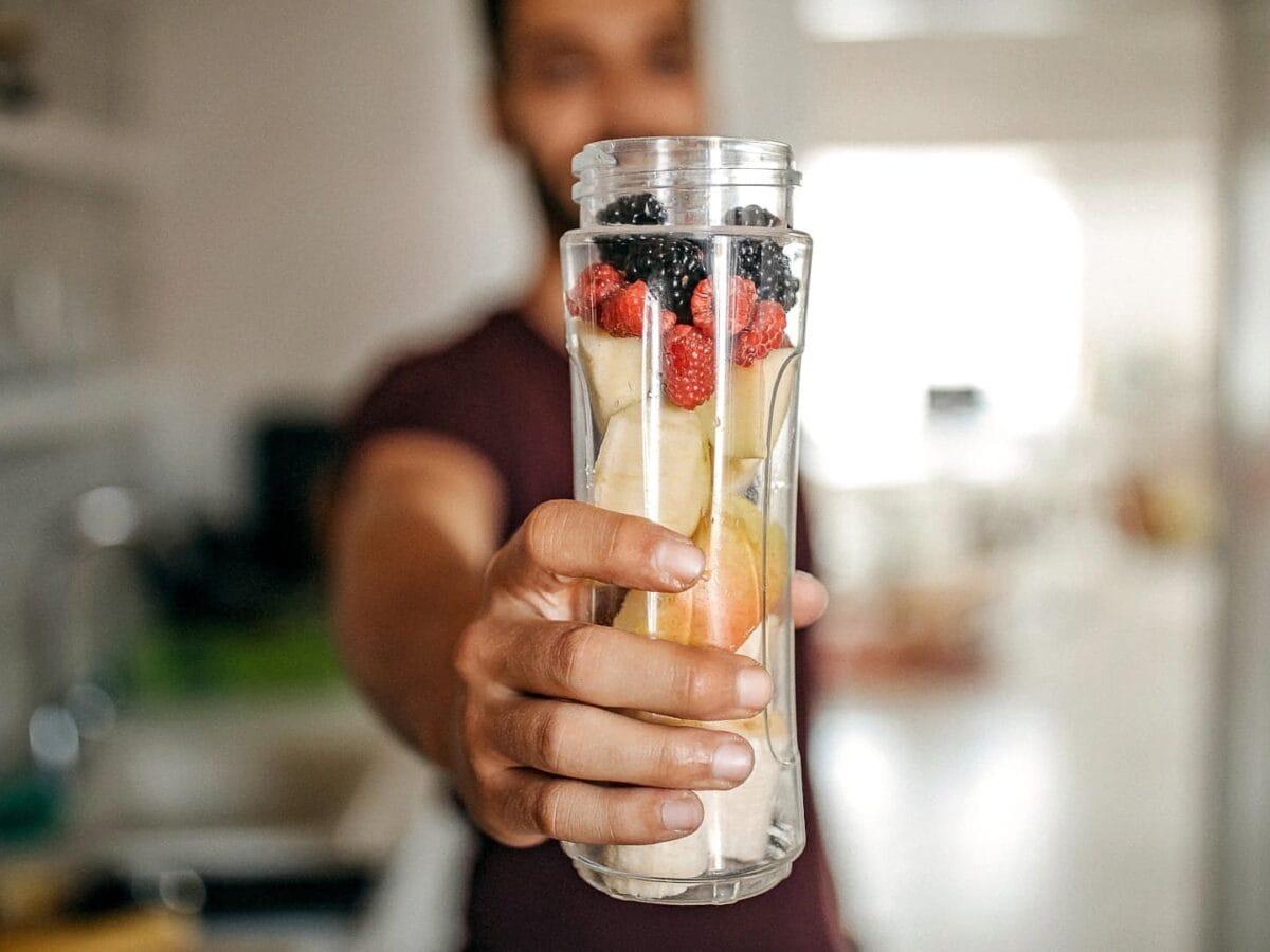 Mann hält einen Smoothiemixer voll Früchten in die Kamera.