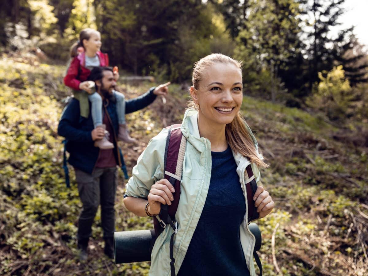 Eine dreiköpfige Familie, die mit Rucksack und Isomatte durch einen Wald wandert.