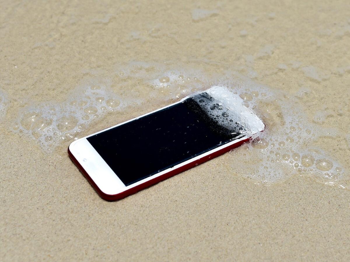 Smartphone liegt am Strand und wird von Meerwasser überspült.