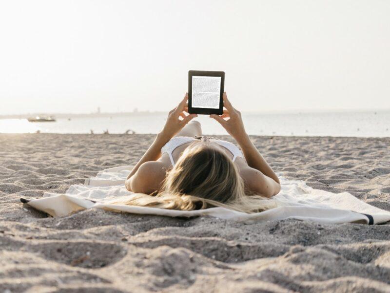 Frau liegt am Strand und liest auf einem EBook-Reader