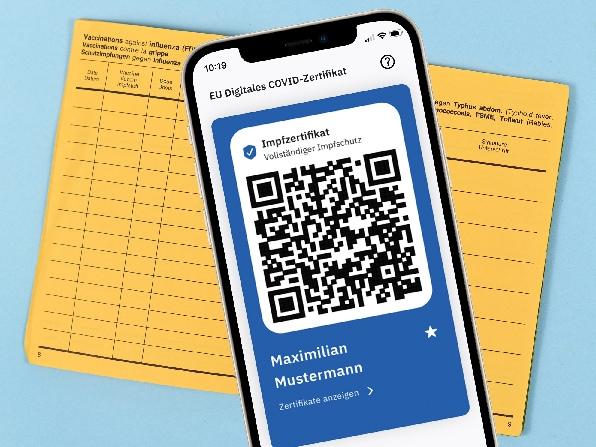 Smartphone mit geöffnetem QR-Code aus CovPass-App liegt auf einem gelben Impfpass.