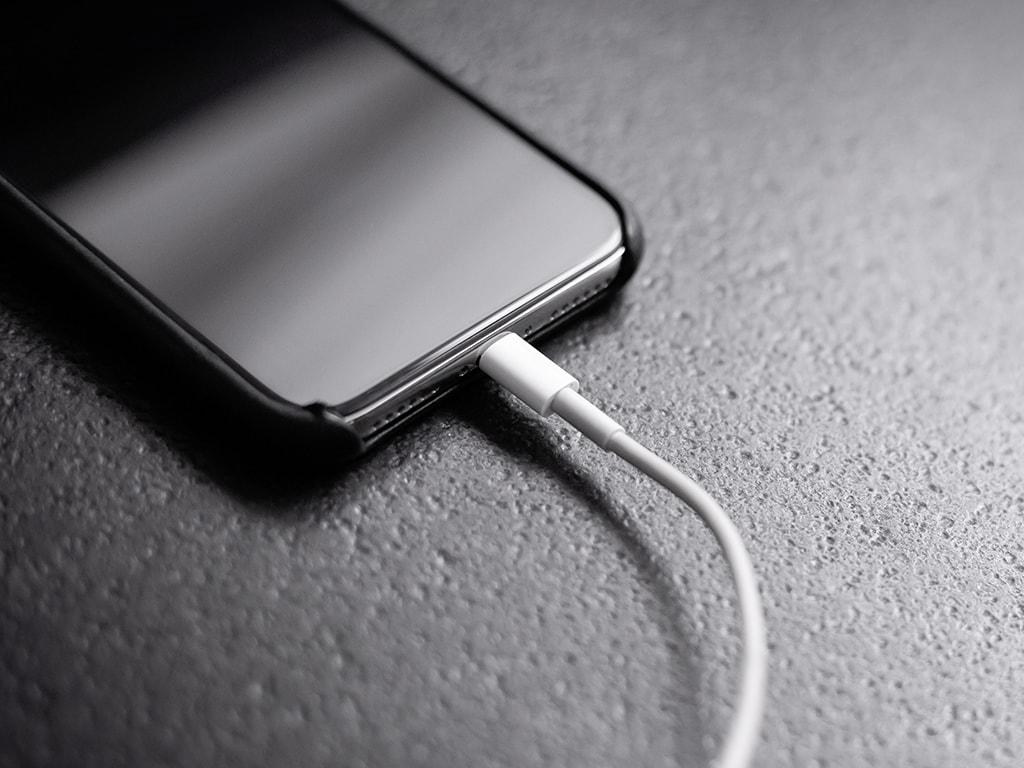 Das iPhone mit angestecktem Ladekabel.