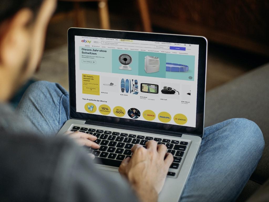 Ein Mann nutzt die Verkaufsplattform eBay auf seinem Laptop