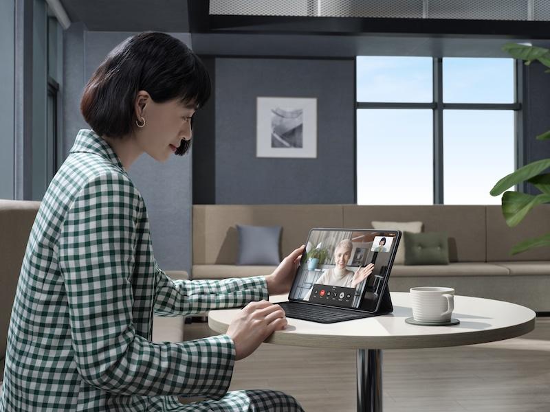Eine Frau an einem Tisch bedient einen Tablet-Computer.