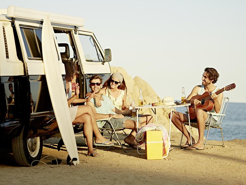 Menschen sitzen am Strand neben VW-Bus