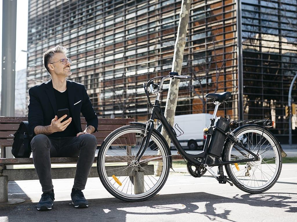 Mann sitzt auf Bank mit E-Bike