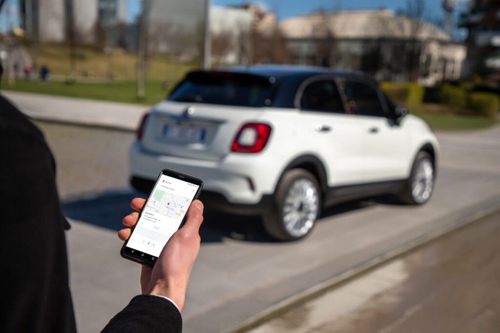 Person mit Smartphone und Standortanzeige in der Fiat-App vor dem Auto