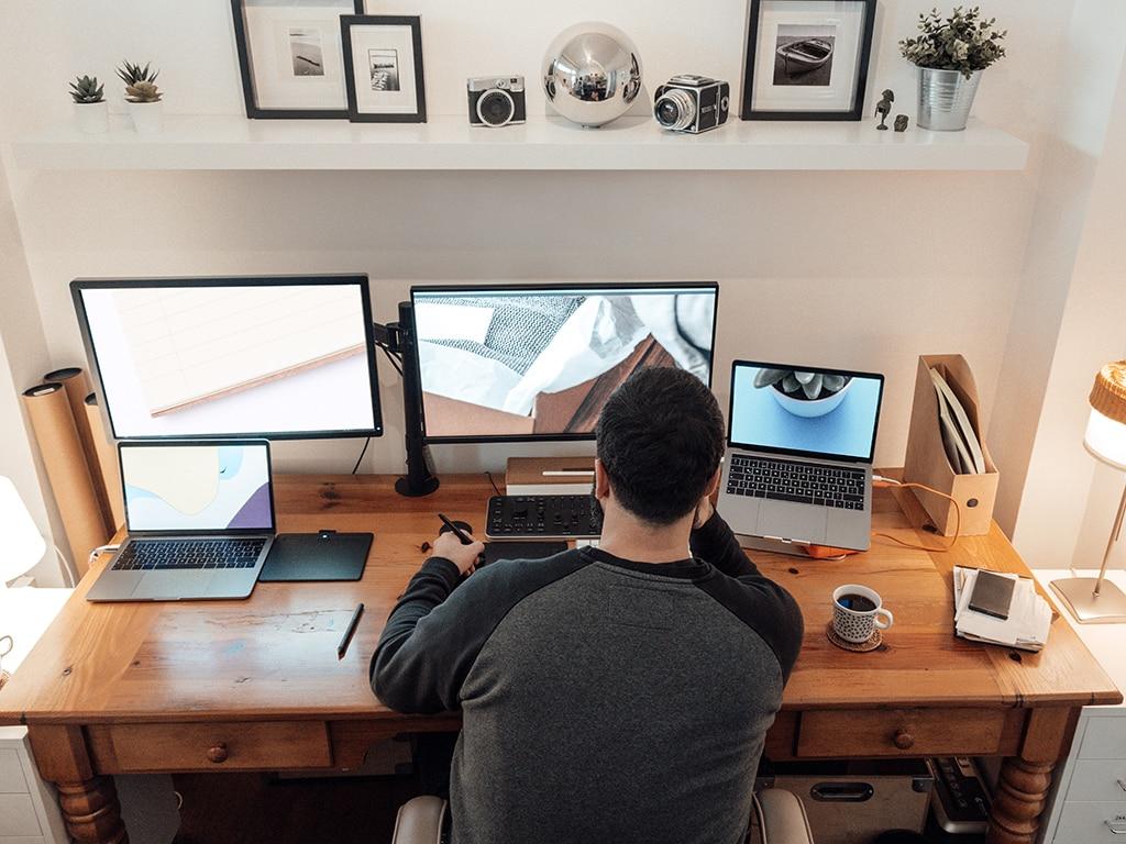 Mann im Home-Office mit zwei Monitoren und Notebooks