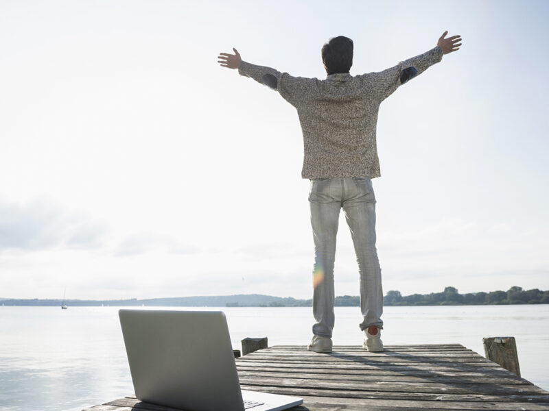 Mann mit Notebook auf Steg am See