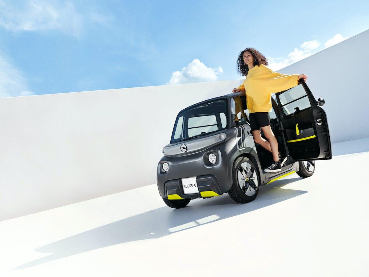 Eine Frau steht vor einem Kleinwagen mit Elektroantrieb.