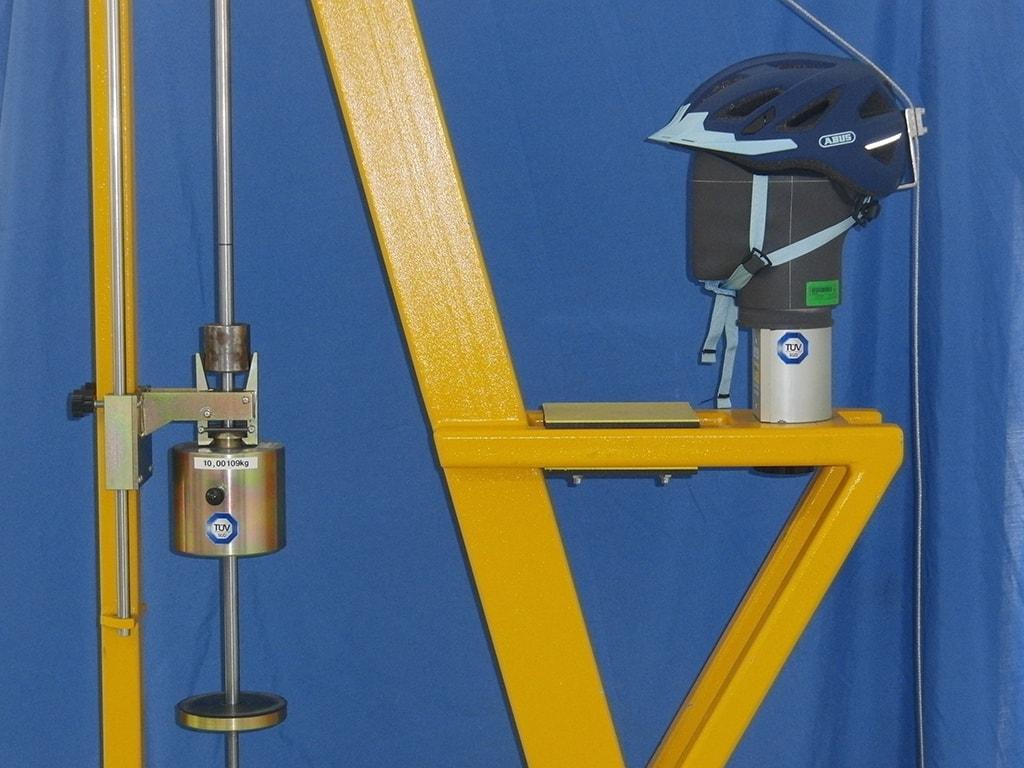 Gelbes Gestell mit Gewicht trägt Dummy-Kopf mit Abus-Helm von der Seite