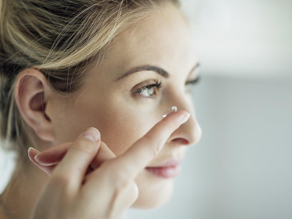 Blonde Frau hält mit Finger eine Kontaktlinse ans Auge, Profil schräg von der Seite