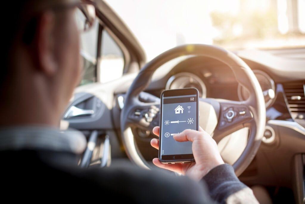 Blick über die Schulter eines Mannes, der im Auto sitzt und sein Smartphone bedient
