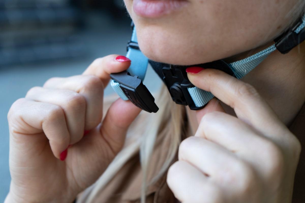 Frauenhände halten Fahrradhelm-Verschluss unter Kinn