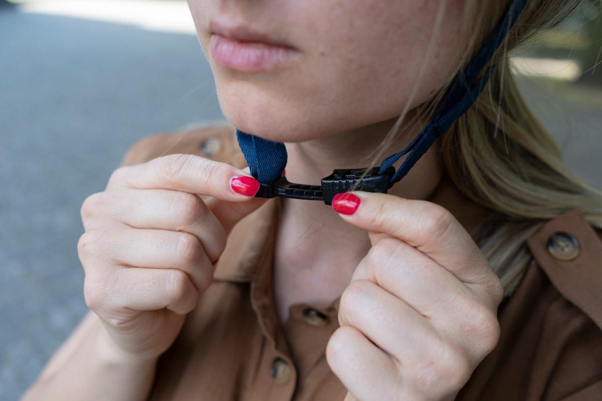 Frauenhände schließen Verschluss von aufgesetztem Giro-Helm