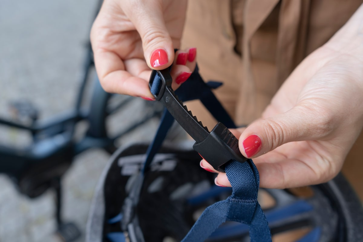 Frauenhände zeigen Verschluss von Giro-Helm