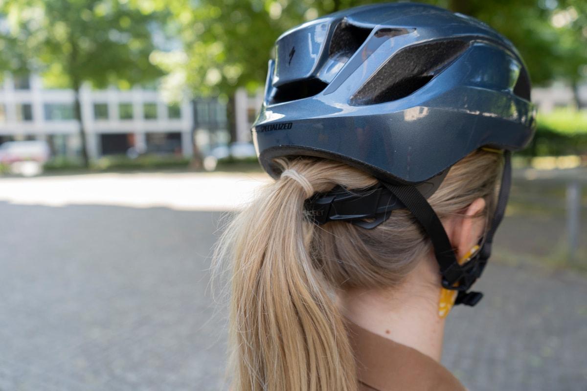 Frau trägt Zopf unterm Align 2-Helm von hinten