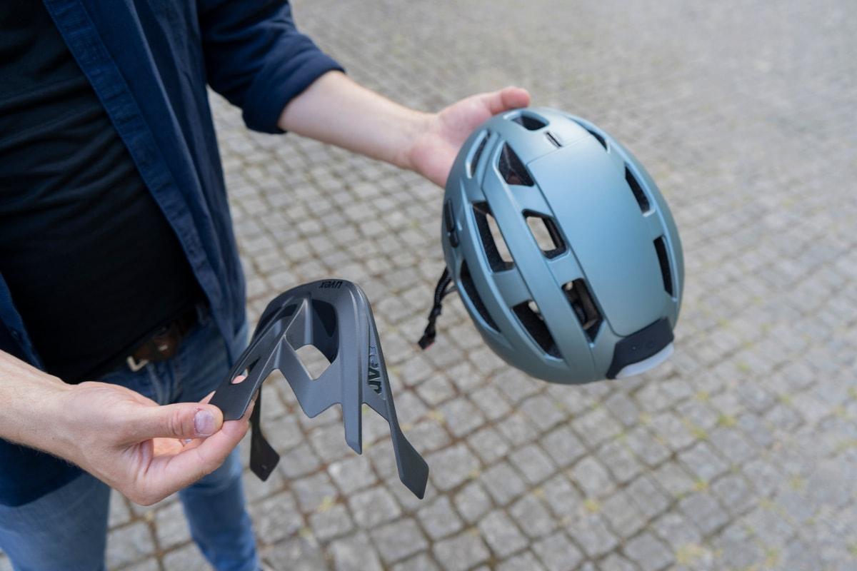 Männerhände halten Uvex-Helm und Schutzteil