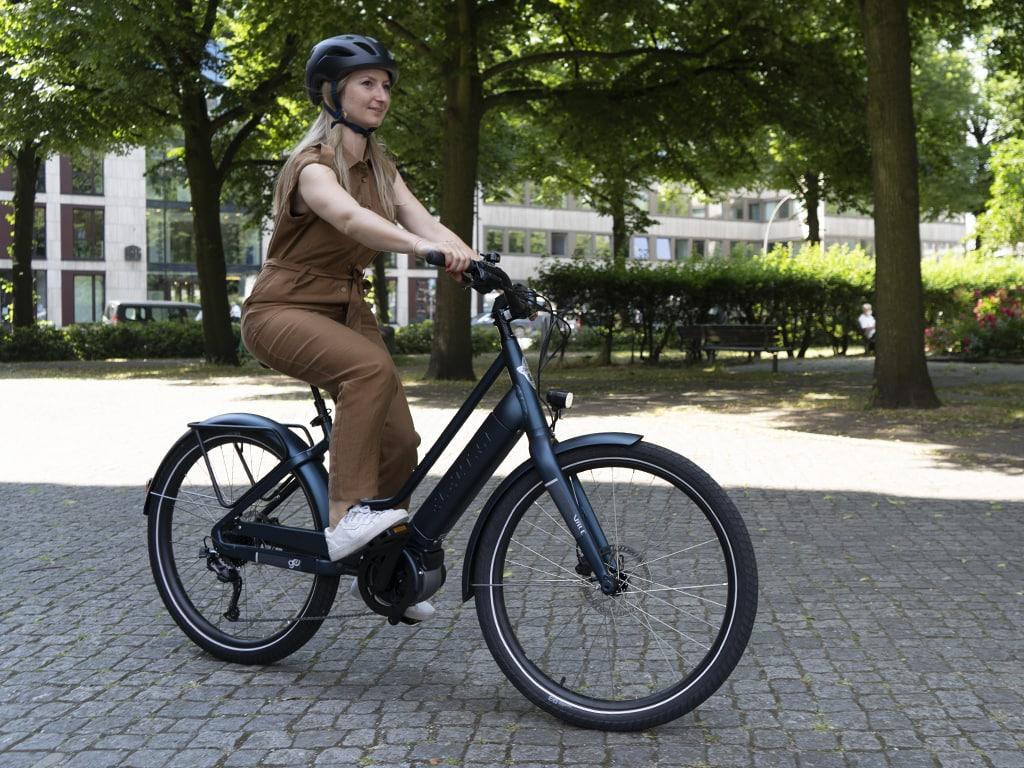 Frau auf dunklem E-Bike fährt auf Pflasterweg
