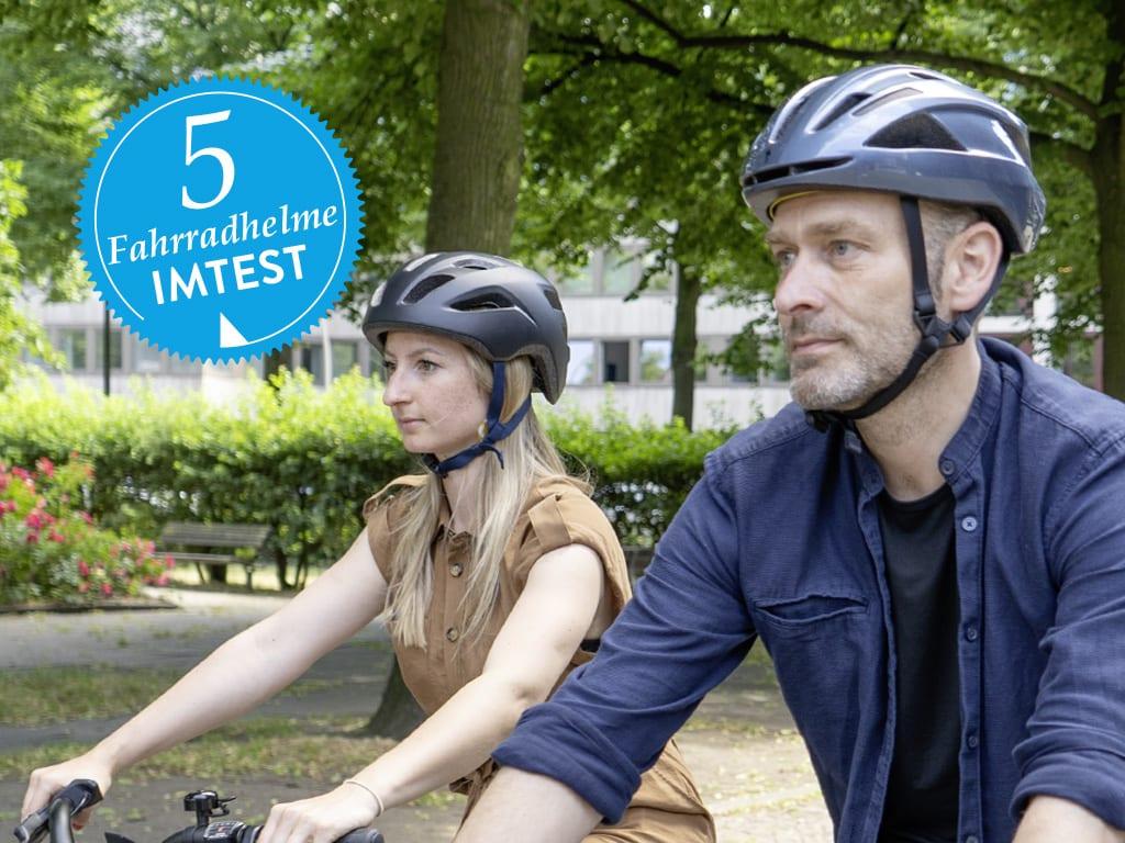 Frau und Mann mit Fahrradhelmen fahren Fahrrad.