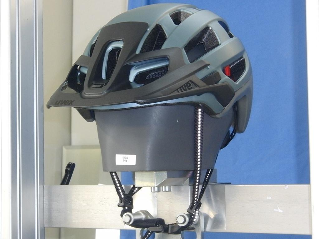 Uvex-Helm schräg von vorn auf Metallkopf mit gestreckten Kinnriemen