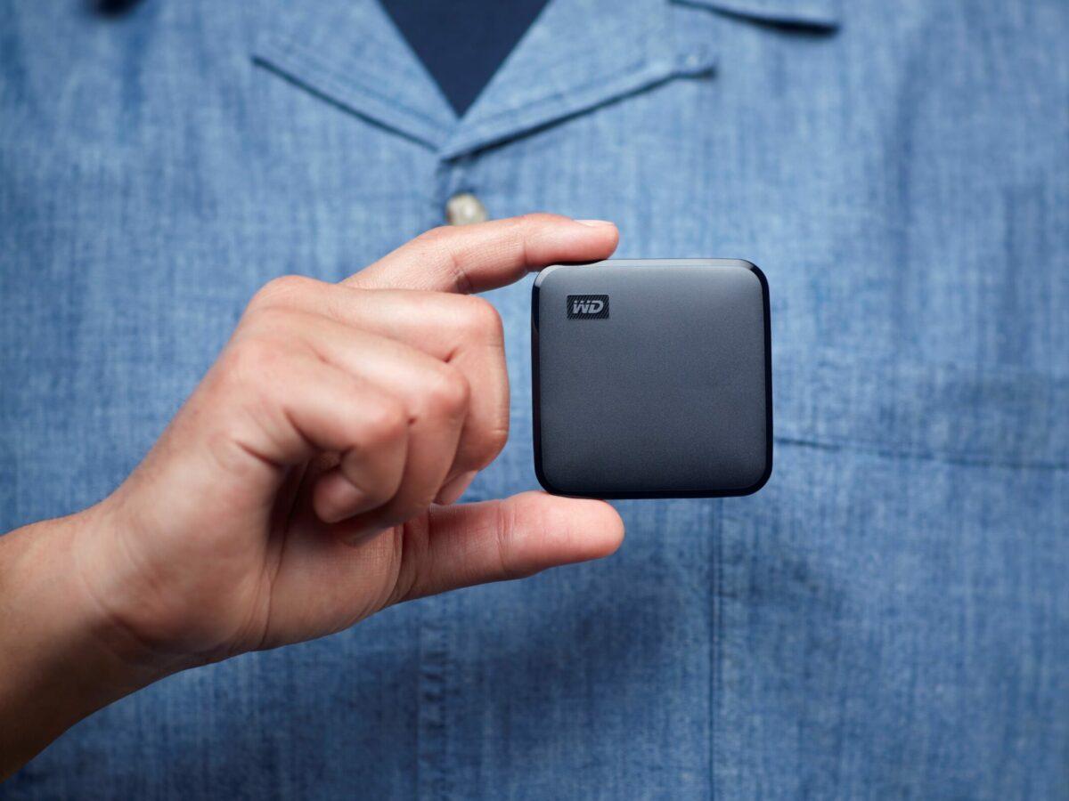 Ein Mann hält eine SSD-Festplatte in der Hand.