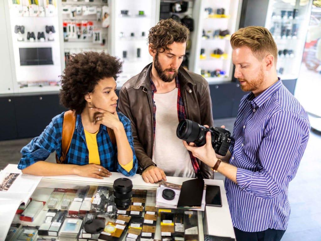 Elektronikgeschäft mit zwei Kunden, die sich beraten lassen
