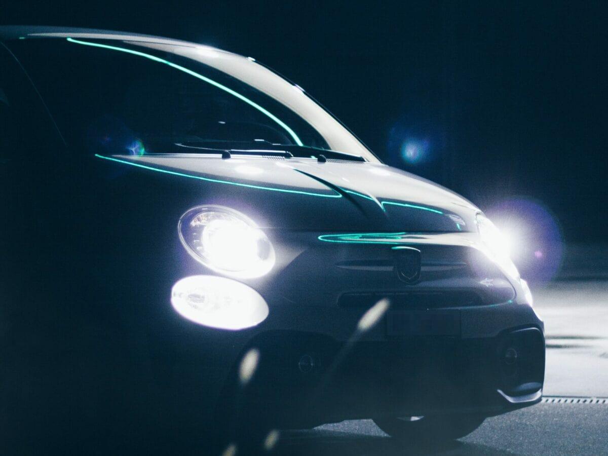 Ein Auto bei Nacht mit leuchtenden Scheinwerfern.