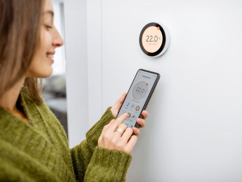 Junge Frau von der Seite bedient Smartphone und steht vor weißer Wand mit rundem Thermostat