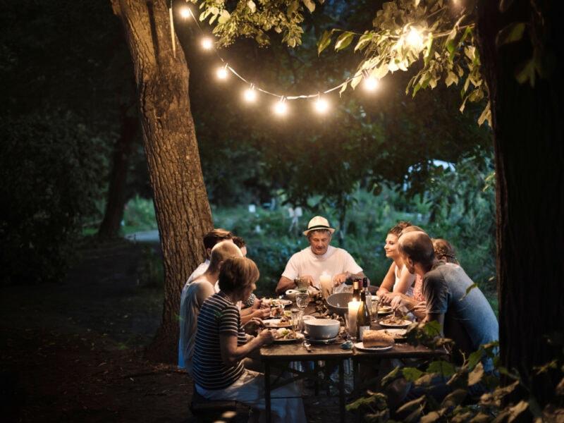 Freunde am gedeckten Tisch im Garten bei Dunkelheit beleuchtet von Lichterkette