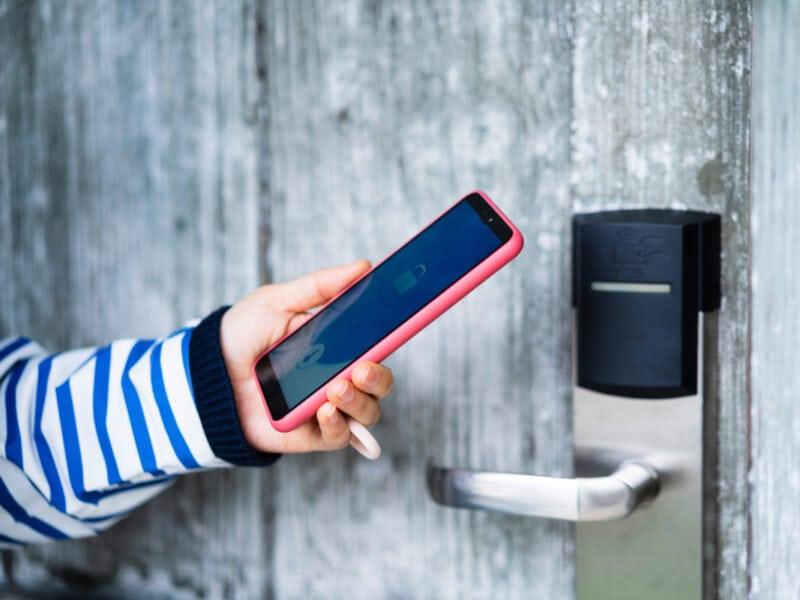 Hand hält Smartphone an smartes Türschloss an grauer Holztür