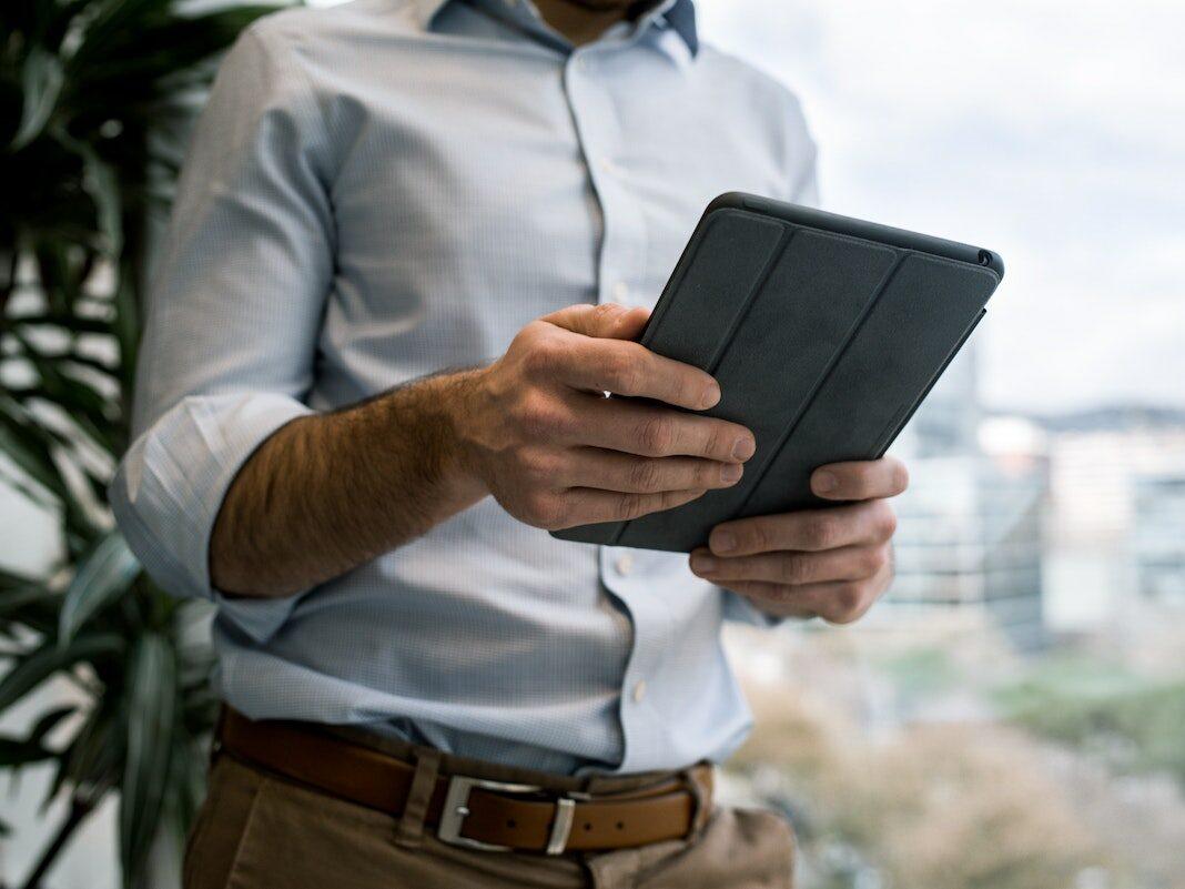 Ein Mann hält ein Tablet in der Hand.