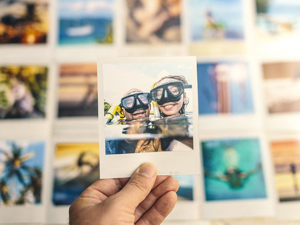 Hand hält ausgedrucktes Urlaubsfotos von zwei Kinderköpfen mit Taucherbrillen im Wasser, im Hintergrund liegen viele weitere in Reihen angeordneten Fotos