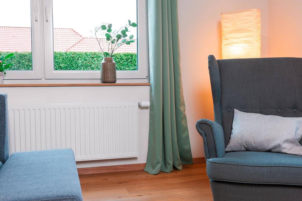 Wohnzimmer mit Heizung an der ein smartes Thermostat angebracht ist