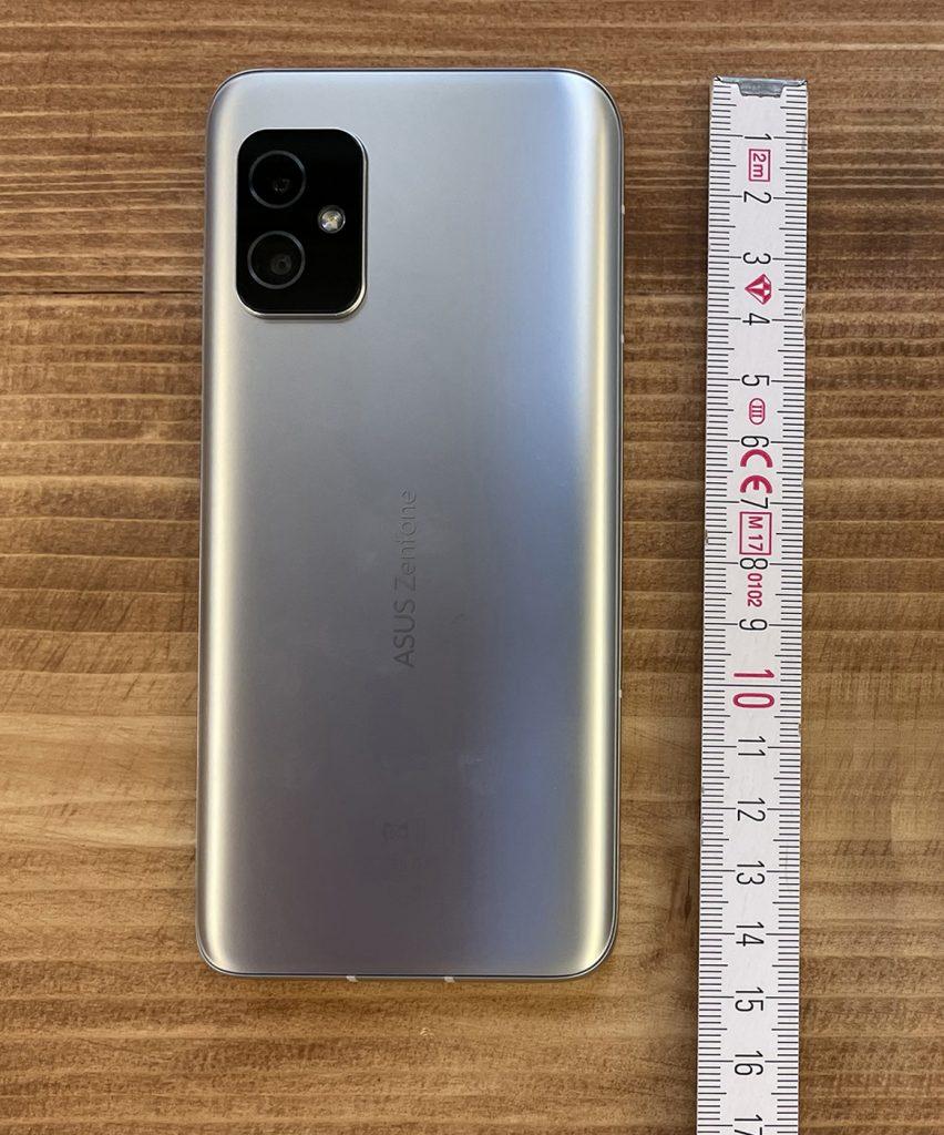 Blaues Smartphone neben Zollstock auf Holzboden