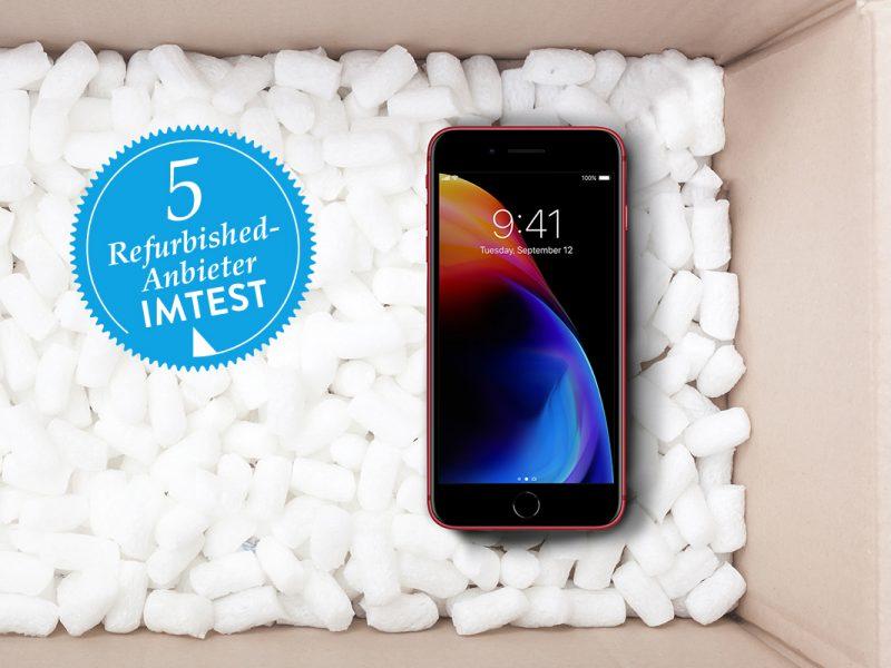 Blick in Karton mit weißem Füllmaterial und schwarzem Smartphone mit buntem Bild auf Display