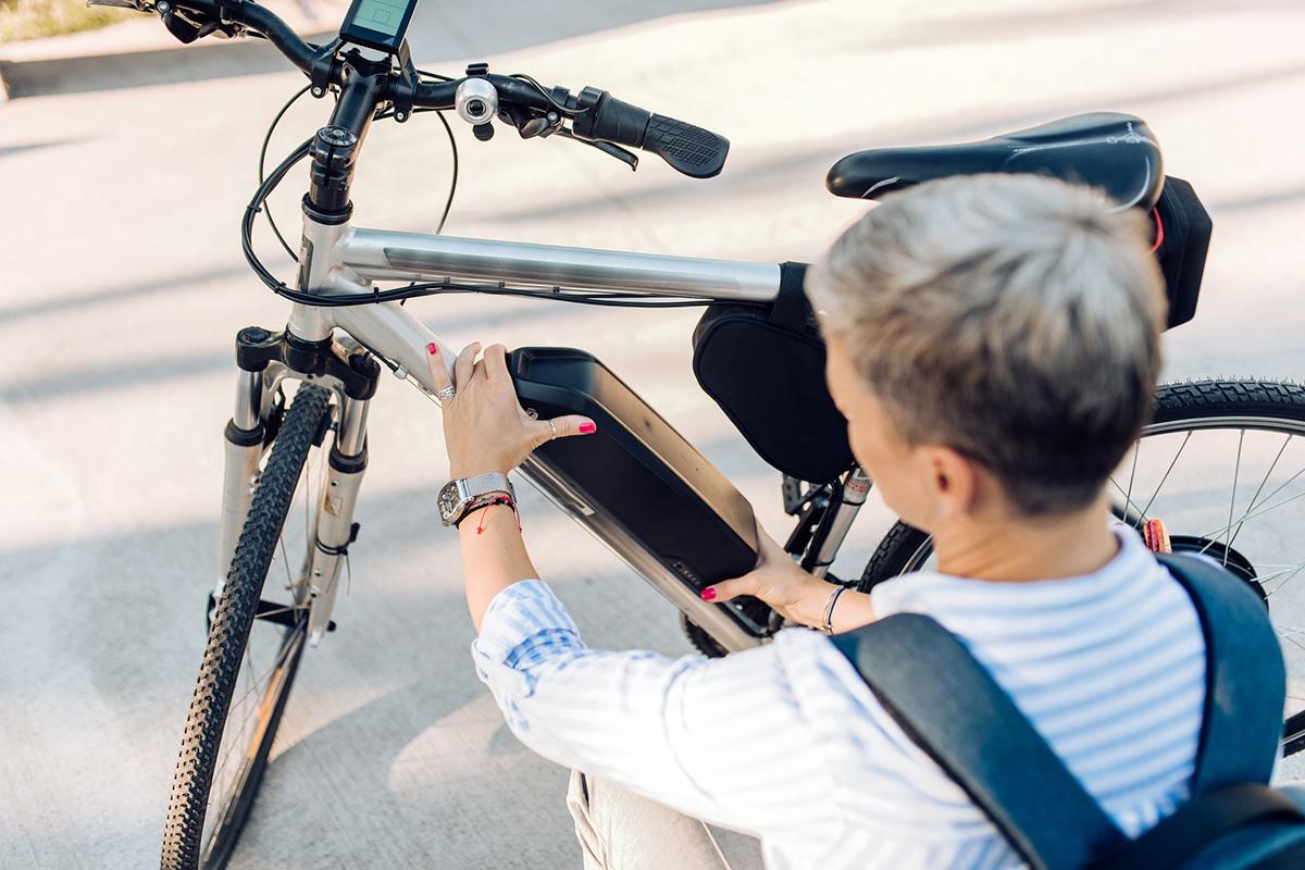 Frau setzt Akku in E-Bike ein.