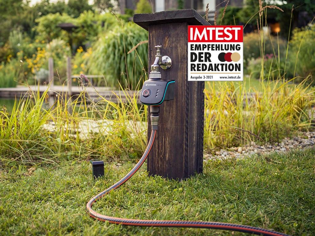 Rasenfläche mit in Holz verkleidetem Wasseranschluss mit angeschlossenem Schlauch, IMTEST-Empfehlungssiegel