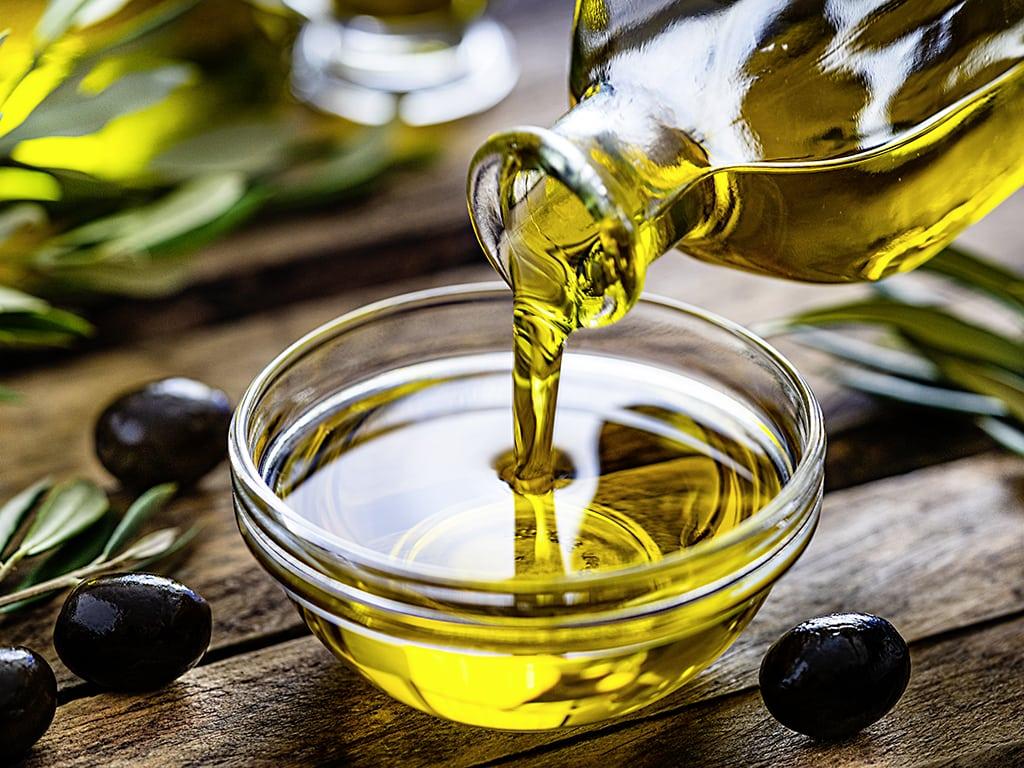 Olivenöl wird aus Glasflasche in Glasschüssel gekippt, steht auf Holztisch mit Olivenzweige drauf
