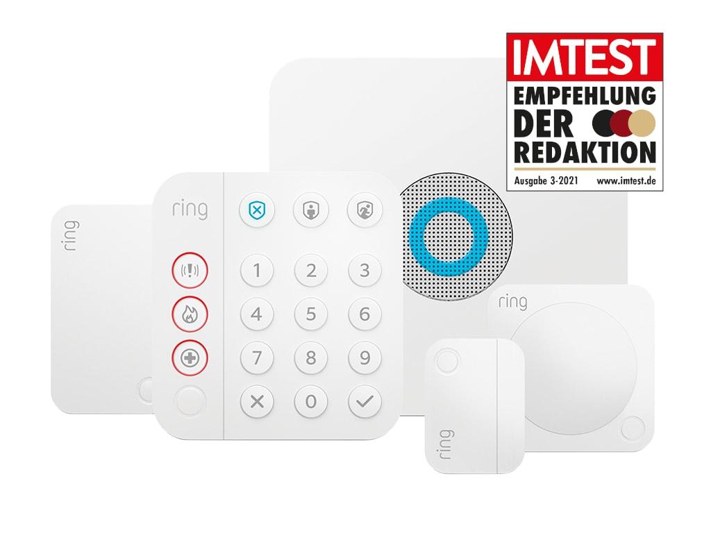 Fünf weiße Geräte von Ring Alarm angeordnet auf weißem Hintergrund mit IMTEST-Empfehlungssiegel