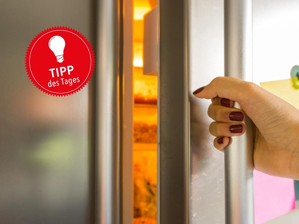 Eine Hand öffnet einen Kühlschrank