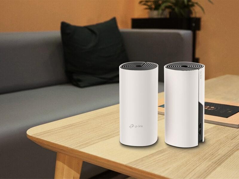 Auf Kante von Holztisch stehen zwei weiße Zylinderförmige Geräte, im Hintergrund ein graues Sofa