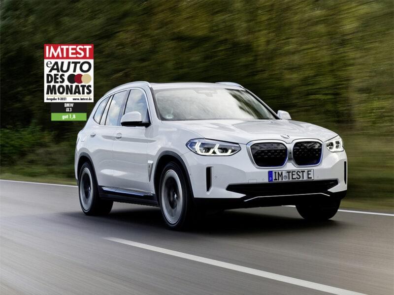 Silberner SUV von BMW fährt auf Straße am Wald mit dem IMTEST-Siegel