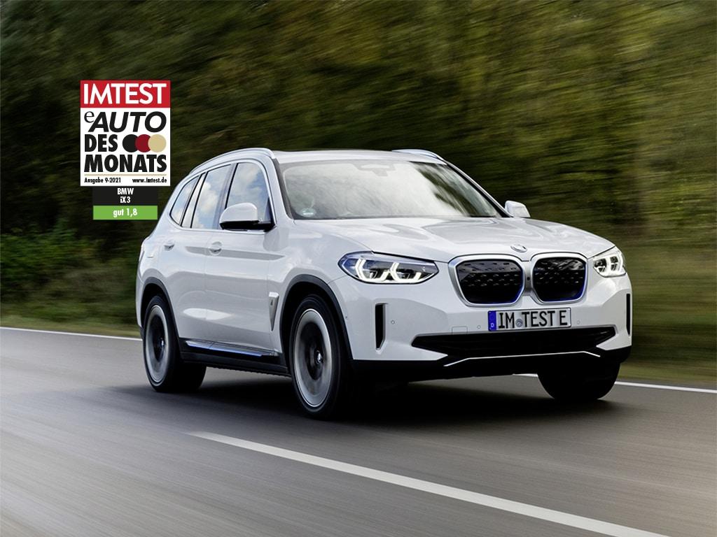 """Silberner SUV von BMW fährt auf Straße am Wald mit dem IMTEST-Siegel """"E-Auto des Monats"""""""