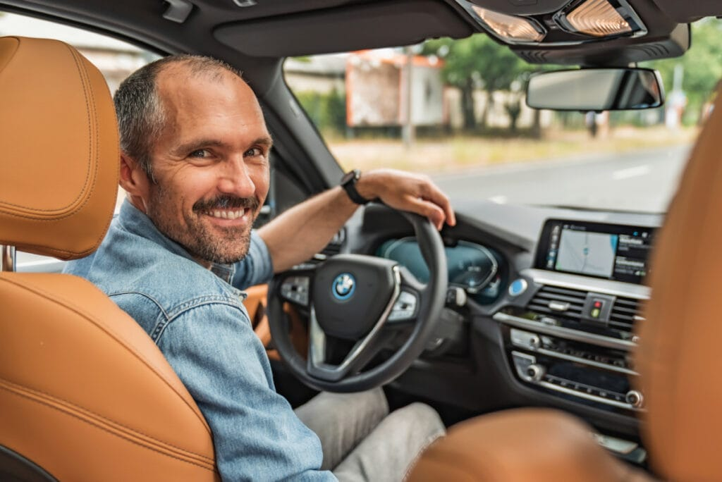 Mann auf Fahrersitz im Auto schaut lächelnd über die Schulter nach hinten