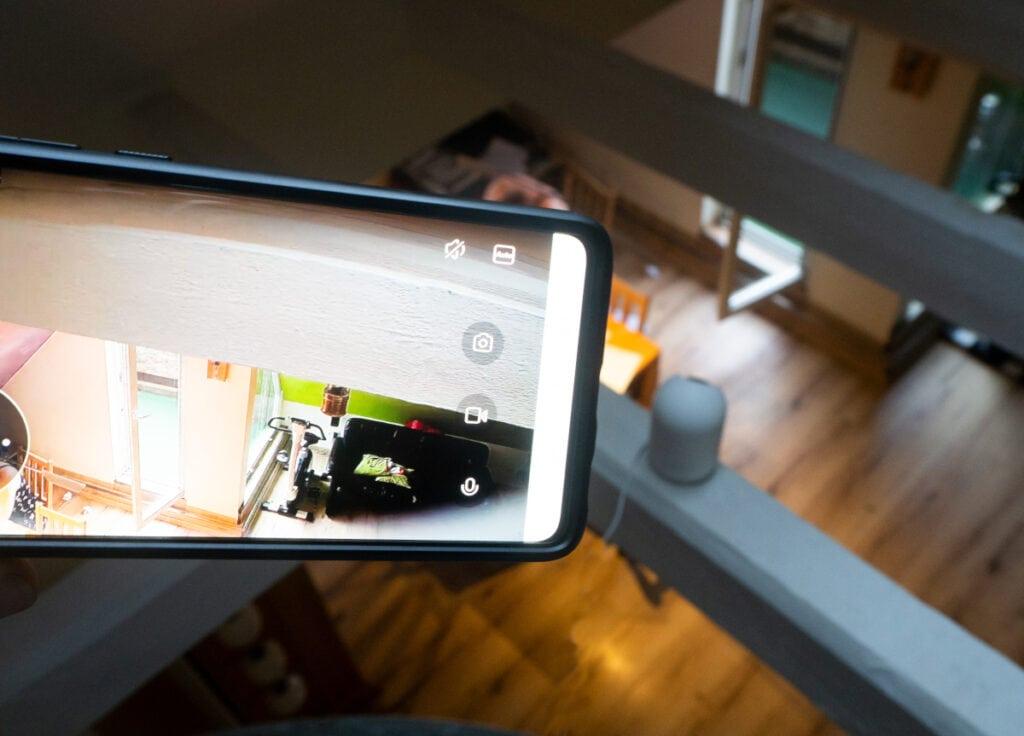 Smartphone ragt von links ins Bild und zeigt Aufnahme der Überwachungskamera, die dadrunter auf einem Balken platziert ist