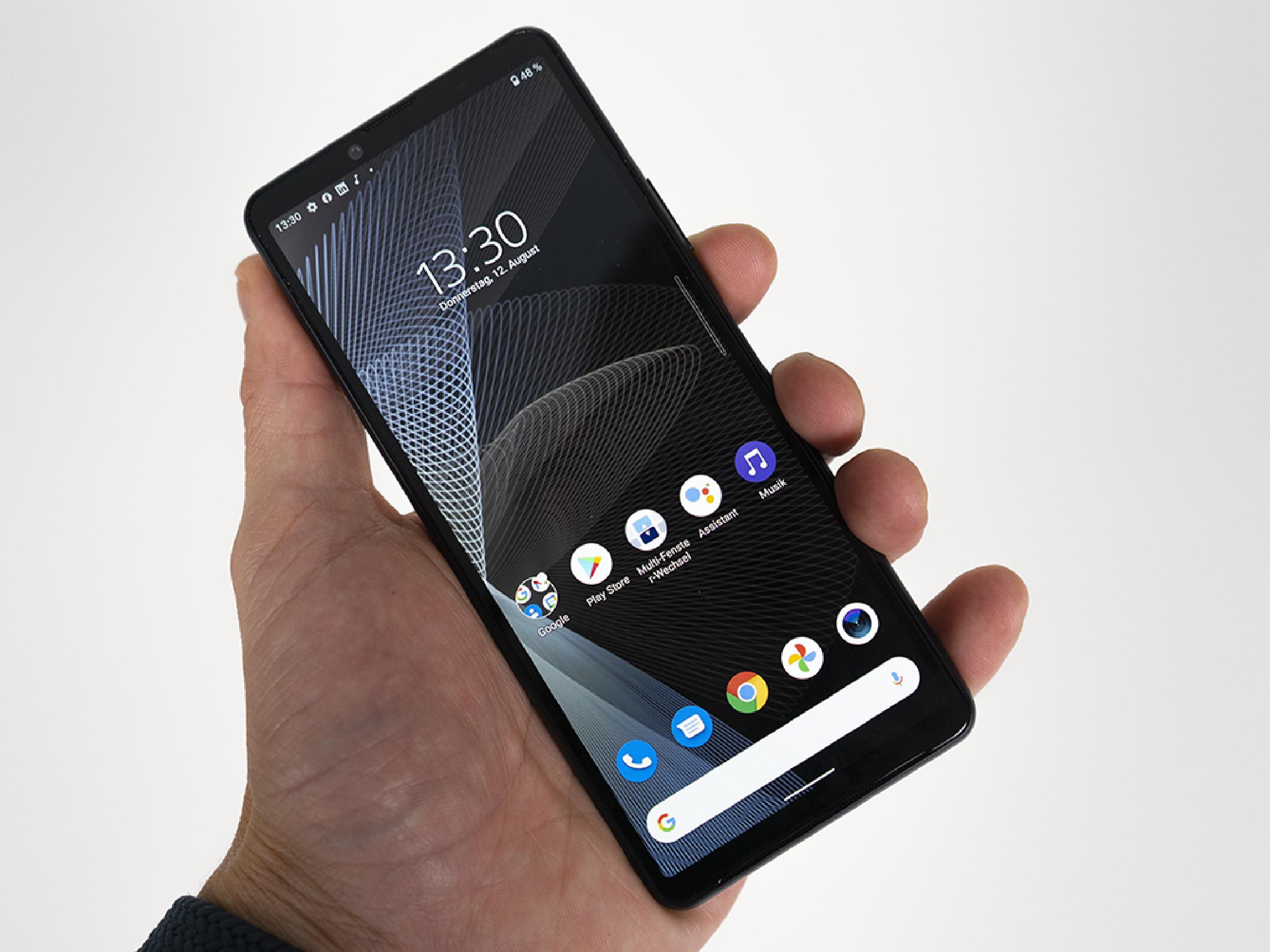 Hand hält Smartphone mit Startbildschirm vor grauer Wand