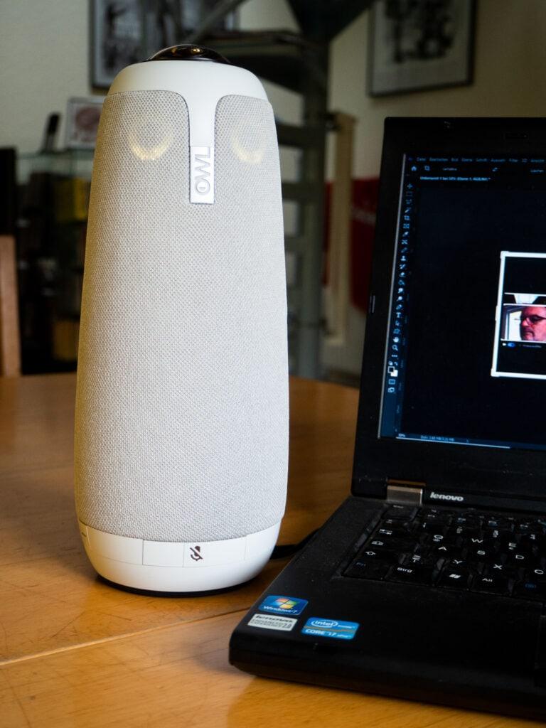 Weiß graues zylinderförmige Meeting Owl Pro auf Holztisch, rechts ein aufgeklapptes Notebook